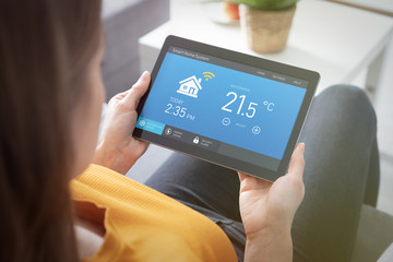Woman using smart home application on tablet.