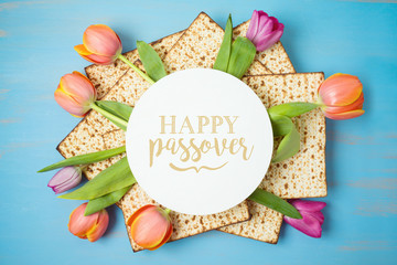 Jewish holiday Passover greeting card with matzah and tulip flowers on wooden table. Pesach background.
