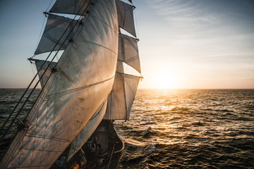 Old tall ship sails backlit