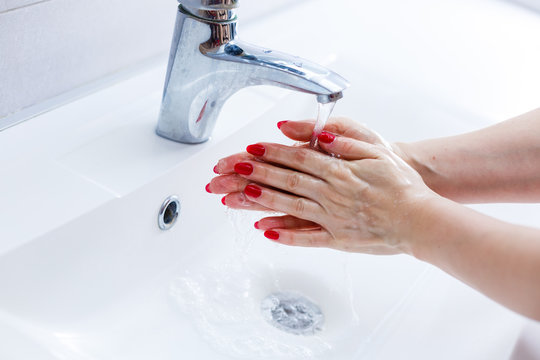 Washing hands in a public restroom (focus on the tap, hands in motion)