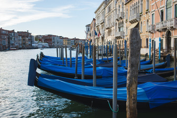 Foto op Aluminium Gondolas Traditional venetian gondolas by the waterfront. Several boats for travelers and tourists are covered with covers at the pier.