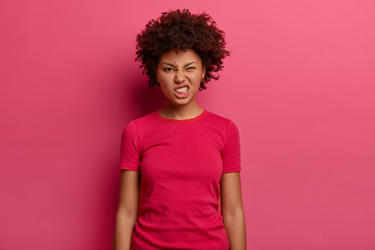 Annoyed dissatisfied woman clenches teeth and feels irritated, looks in displeasure at camera, dressed in casual t shirt, poses indoor against pink background. Negative face expressions concept