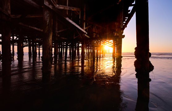 Setting sun shines through the pilings under Crystal Pier at low tide