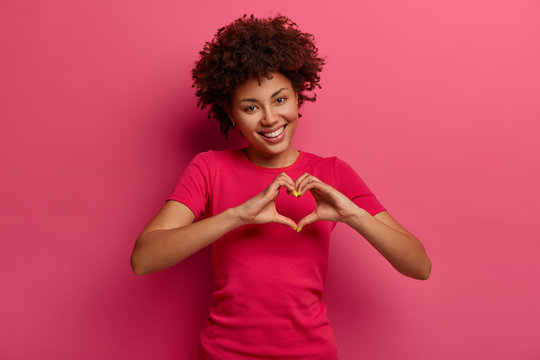 Pretty curly African American woman confesses in love, makes heart gesture, shows her true feelings, has happy expression, wears casual red t shirt, poses over pink background. Relationship concept