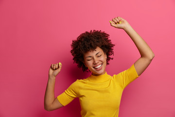 Beautiful dark skinned young woman feels relaxed and relieved, dances carefree, raises arms in air, smiles positively, dressed casually, poses against pink background. Happy lifestyle concept Fotobehang