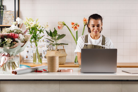 Young flower shop owner using laptop at counter. Woman florist standing at table.