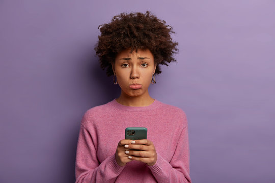 Unhappy disappointed woman with Afro hair, purses lower lip, holds smartphone, sad to miss chance of good shopping sale, upset not to receive call from boyfriend, poses indoor, dressed casually