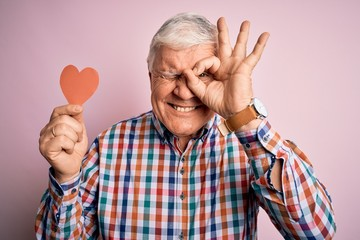 Senior handsome hoary romantic man holding red paper heart shape over pink background with happy face smiling doing ok sign with hand on eye looking through fingers Fotobehang