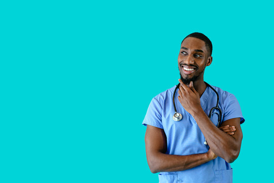 Portrait of a smiling male doctor or nurse thinking and looking to side at copy space