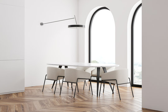 White dining room corner with arched windows