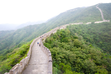 A view along the Great Wall of China, with a few tourists, and the surrounding hills covered by low cloud.