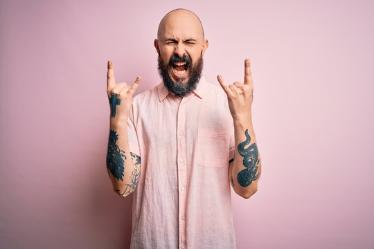 Handsome bald man with beard and tattoo wearing casual shirt over isolated pink background shouting with crazy expression doing rock symbol with hands up. Music star. Heavy concept.