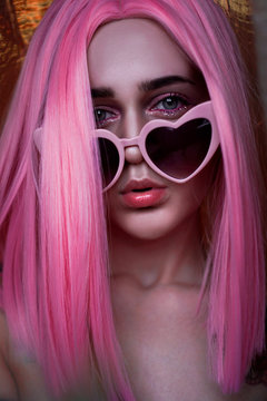 Portrait of teenage model with pink hair. Funky teenager wearing color wig and trendy glasses. Vertical photo - good format for stories
