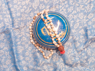 Blue and golden singing bowl with a mallet neckless on an Indian scarf