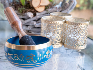 blue and golden indian singing bowl made of seven metals with a wooden striker on a glass table, plants in background