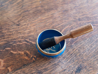 blue and golden indian singing bowl made of seven metals with a wooden striker on a wooden table