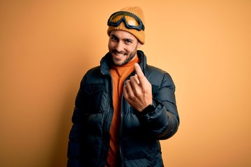 Young handsome skier man with beard wearing snow sportswear and ski goggles Beckoning come here gesture with hand inviting welcoming happy and smiling