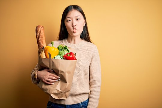 Young asian woman holding paper bag of fresh healthy groceries over yellow isolated background making fish face with lips, crazy and comical gesture. Funny expression.