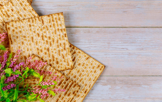 Jewish matzah bread with flowers on wooden rustic background. Passover holiday concept
