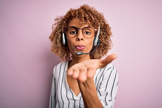 African american curly call center agent woman working using headset over pink background looking at the camera blowing a kiss with hand on air being lovely and sexy. Love expression.