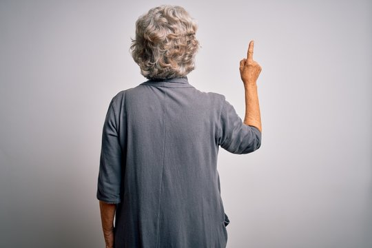 Senior beautiful grey-haired woman wearing casual dress standing over white background Posing backwards pointing ahead with finger hand