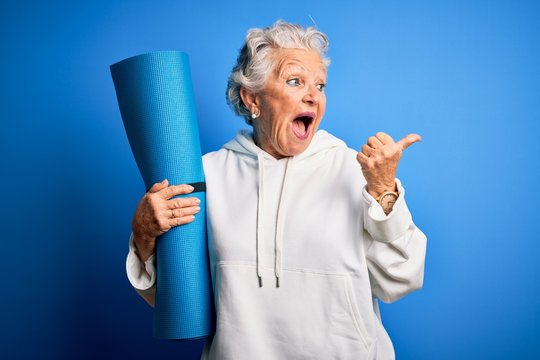 Senior beautiful sporty woman holding mat for yoga standing over isolated blue background pointing and showing with thumb up to the side with happy face smiling