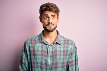 Young handsome man with beard wearing casual shirt standing over pink background smiling looking to the side and staring away thinking. Fotomurales