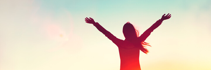Happy woman sihouette with arms raised up in success on sunset glow sunshine banner panorama. Wellness, financial freedom, healthy life concept background.