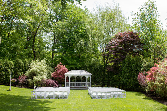 A pretty wedding ceremony location with a gazebo and flowering trees surround.