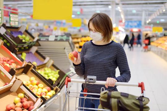 Young woman wearing disposable medical mask shopping in supermarket during coronavirus pneumonia outbreak