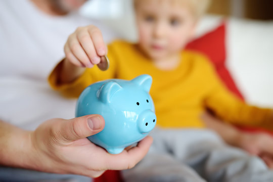 Father and child putting coin into piggy bank. Education of children in financial literacy