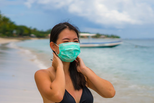 use of medical face mask in public places- young attractive Asian Korean woman enjoying beach holidays in bikini and protective facial mask in prevention vs virus infection