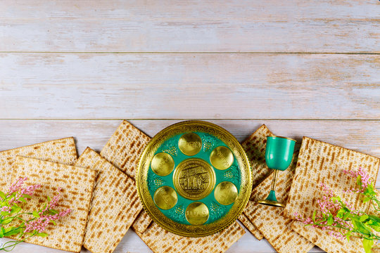 Jewish matzah, kiddush and seder with text in hebrew egg, bone, herbs, karpas, chazeret and charoset. Passover concept.