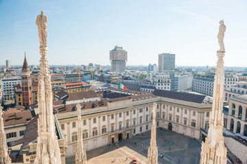 Tuinposter Milan White statue on top of Duomo cathedral and view to city of Milan