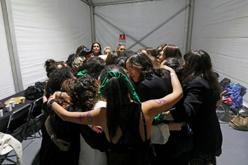 """Members of the female collective of Latin-American singers and authors 'El Palomar' embrace before a rehearsal of a """"Song Without Fear"""", a song against femicide, at Zocalo square, in Mexico City"""
