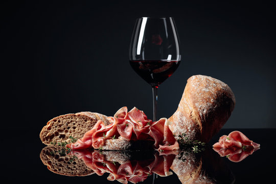 Prosciutto with ciabatta, red wine and thyme on a black background.