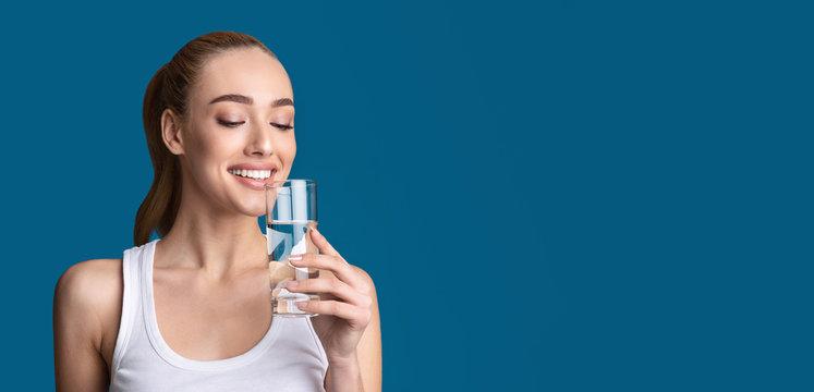 Cheerful Woman Drinking Water From Glass Standing, Studio Shot, Panorama