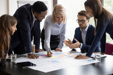 Happy motivated diverse businesspeople work together cooperate at business office meeting, smiling...