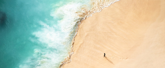 View from above, stunning aerial view of a person walking on a beautiful beach bathed by a turquoise sea during sunset. Kelingking beach, Nusa Penida, Indonesia. Fototapete