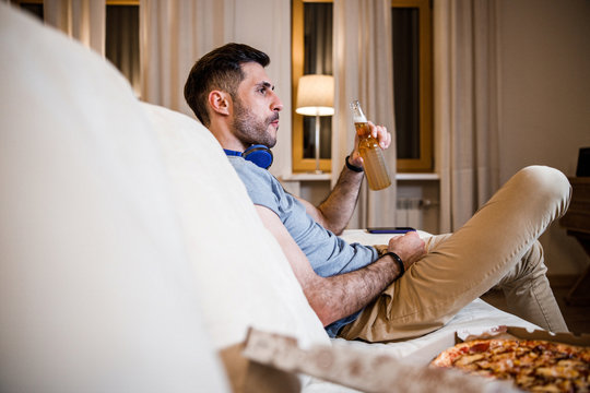 Bachelor enjoying unhealthy meal at home stock photo