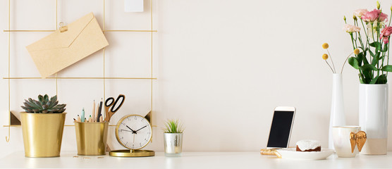 Stylish desk interior with White table background with plant and leaves. Modern home office interior panoramic banner backdrop