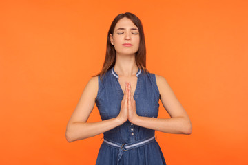 Printed roller blinds Zen Mindfulness, zen practice. Happy calm brunette woman in denim dress doing yoga exercise with hands together, meditating, feeling tranquil relaxed. indoor studio shot isolated on orange background