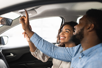 Couple Sitting In Car Pushing Buttons Testing Auto In Dealership