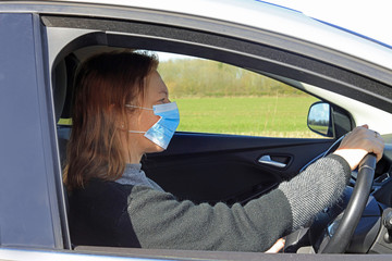 woman in car wearing a face mask.
