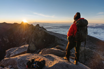 a man with backpack enjoying sunrise over the clouds on Kota Kinabalu summit in Malaysia. Travel lifestyle, adventure and outdoor activity Wall mural