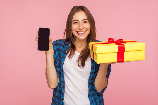 Order delivery online! Portrait of happy pretty girl in checkered shirt holding gift box, cell phone and smiling to camera, advertising gifts and bonuses in mobile application. studio shot, isolated