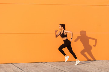 Photo sur Plexiglas Jogging Motivated confident fit woman athlete in tight sportswear, black pants and top, starting to run, jogging outdoor against orange wall, advertising area. Health care and weight loss, sport activity