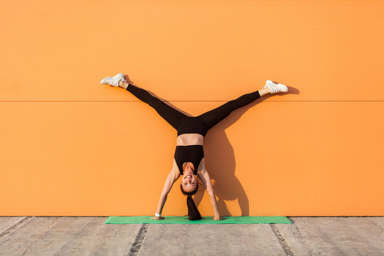 Glad happy humorous girl with perfect athletic body in tight sportswear doing yoga handstand pose with spread legs against wall and showing tongue, having fun. Gymnastics for body balance, flexibility