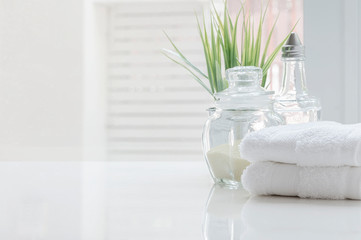 White folded towels and glass bottle on white table with copy space on blurred bathroom background.