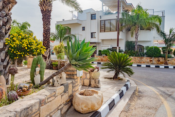 Fotobehang Cyprus Cyprus. Kuklia. Aphrodite's Rock. Petra tou Romiou. The street of the resort. Plants on the streets. Palm trees and cacti. Flora. The Landscape Of The Mediterranean. Residential house in Cyprus.